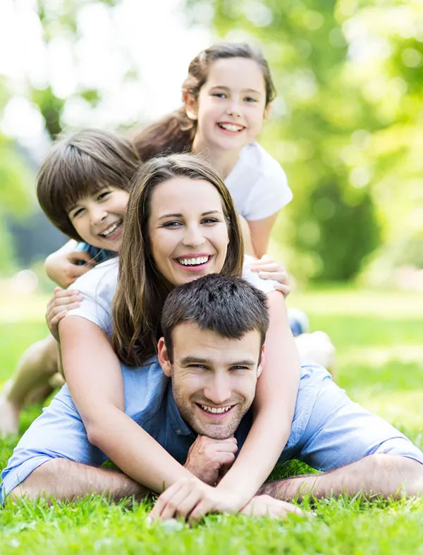 happy family piled on top of each other on the lawn